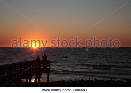 Two beachgoers watch the sunset at Clam Pass Beach in Naples Florida - Stock Photo