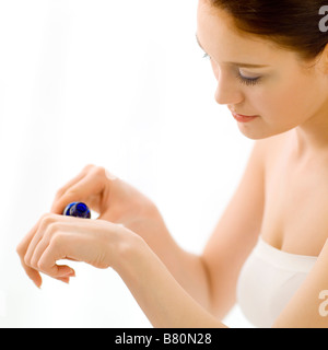 Young woman holding and pouring out a bottle of sensual oil on her hand side view - Stock Photo