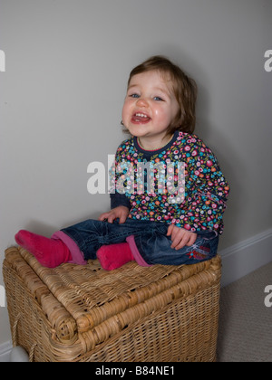 A one year old baby having fun sitting on a wicker toy basket - Stock Photo