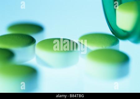 Green pills on white surface - Stock Photo