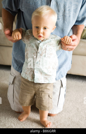 father helping son walk - Stock Photo