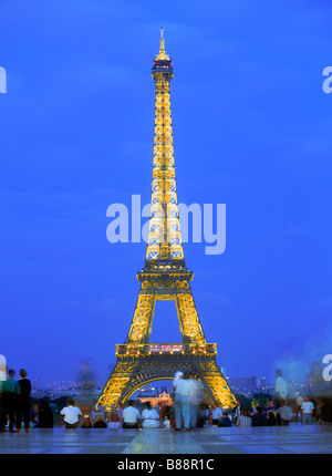 Tourists sightseeing below the Eiffel Tower from the Trocadero at night in Paris, France - Stock Photo