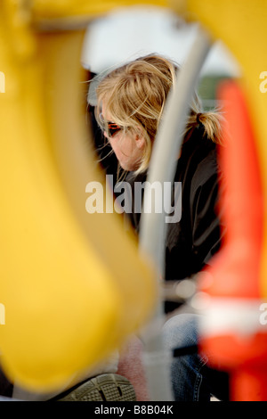 White,European female sailor framed by part of a sailing yacht - Stockfoto