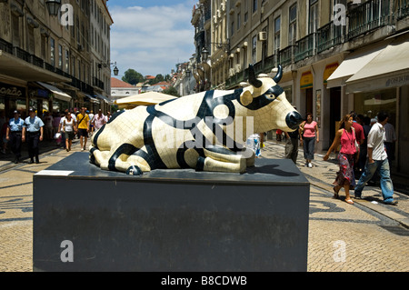 A black and white fibreglass full size cow reclining on a stage in Rua Augusta as part of Cow Parade Lisbon 2006 - Stock Photo