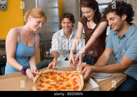 Friends sharing a pizza - Stock Photo