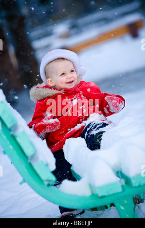 Infant girl playing on a snowcovered park bench at a city park during winter in Anchorage, Alaska - Stock Photo
