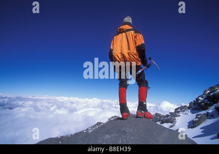 Mountain climber enjoys the view in distance while standing on El Pico de Orizaba in Mexico - Stock Photo
