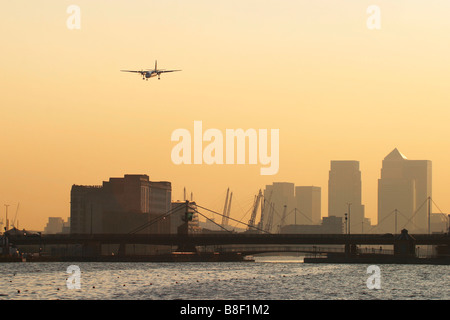 Regional airliner landing at London City Airport with Canary Wharf Docklands in the background, UK - Stock Photo
