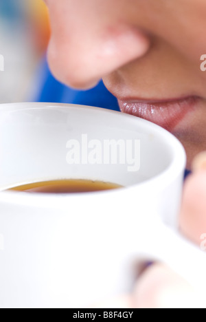 Close up of a woman drinking a hot beverage - Stockfoto
