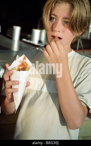 Brown-haired Boy eating Chips out of a little Paperbag - Takeaway - Nutrition - Youth - Stock Photo