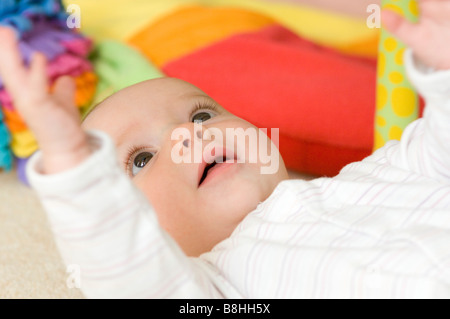 Happy baby playing lying on floor - Stock Photo