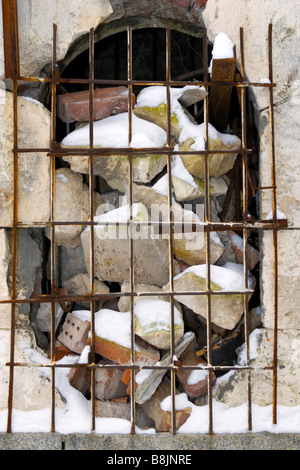 Hole in wall heaped up with stones and bricks. - Stock Photo