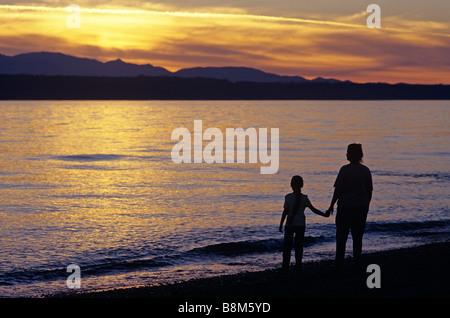 Mother and daughter holding hands along Edmonds Beach at sunset Edmonds Washington State USA - Stock Photo