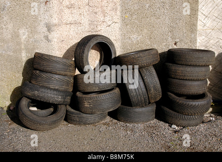 Tyres stacked up against a garage wall. - Stock Photo