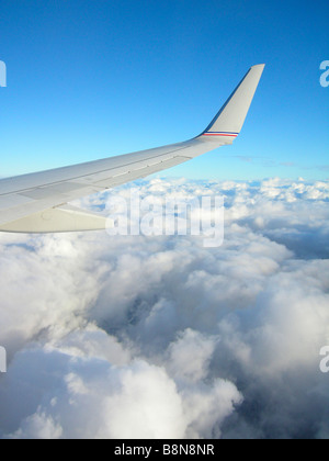 Airplane Wing With Blue Sky & Above Clouds - Stock Photo