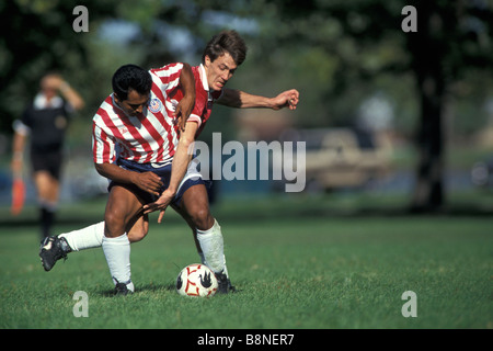 Soccer players fighting for the ball - Stock Photo