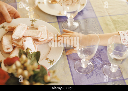 Child reaching for cookies on plate - Stockfoto