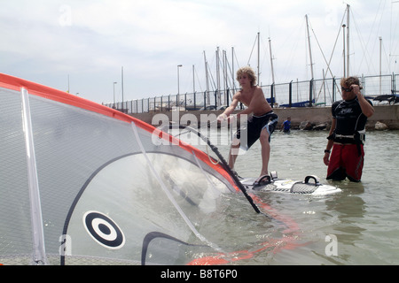 young man giving surf lessons to boy on a surfboard. The boy is trying to lift the sail out of the water, Spain, - Stock Photo