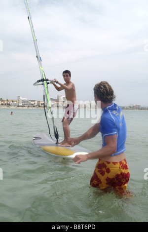 young man giving surf lessons to boy on a surfboard, Spain, Balearen, Majorca - Stock Photo