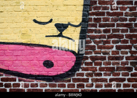 Graffiti of a sad face on a brick wall in Antwerp, Belgium. - Stock Photo