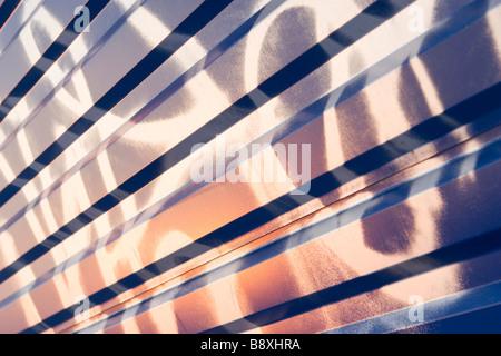 Graffiti painting on waved blue metal sheet pattern on sunset. - Stock Photo