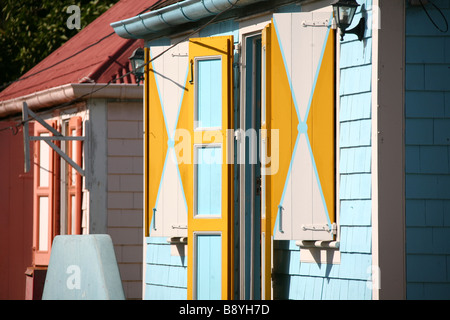 2 houses painted in typical Caribbean bright colours in Orange city on the island Saint Eustace in the Netherlands - Stock Photo