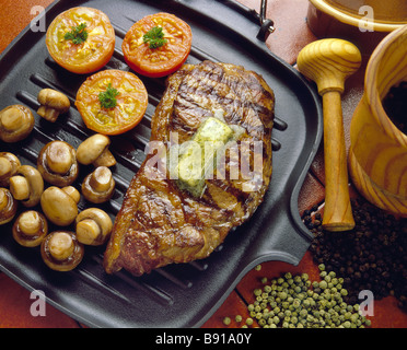 Steak on Griddle pan with mushrooms and tomatoes - Stock Photo