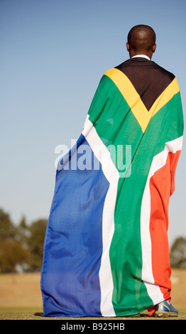 Rear view of a soccer player wrapped up in the South African flag Pretoria Gauteng Province South Africa - Stockfoto