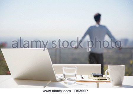 Man taking a break from working on balcony - Stock Photo