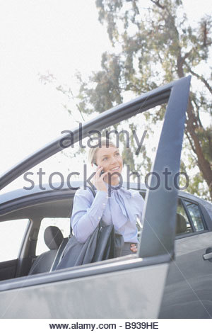 Woman talking on cell phone near car - Stock Photo