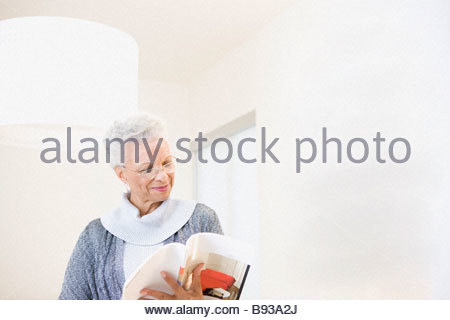 Senior woman reading book at home - Stock Photo