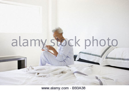 Senior woman reading in bed - Stock Photo