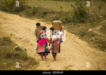 colorful Flower Hmong couples walking home from market in Cau Son near Bac Ha Vietnam - Stock Photo