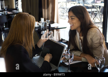 Two young women sitting in cafe, chatting, one using laptop and cell phone - Stock Photo