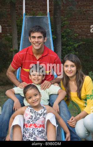 Family smiling on a slide - Stock Photo