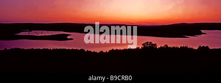 A stunning sunset with a lone sailing boat on Kielder Water in Kielder Forest Northumberland - Stock Photo