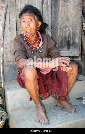 Old Ao Naga Tribe Woman Wearing Necklace And Ear Plugs Sitting Outside Hut - Stock Photo