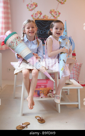 Portrait of two girls holding cardboard cones and smiling on table - Stock Photo