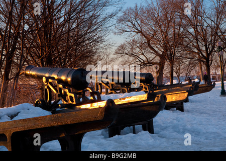 Sun rises over old cannons overlooking the St Lawrence river in Montmorency park in Quebec city - Stock Photo