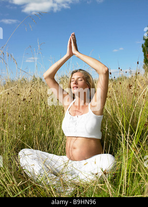 Pregnant woman in a yoga session - Stock Photo