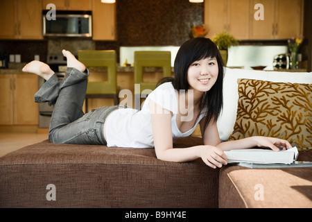Teen girl relaxing with magazine - Stock Photo