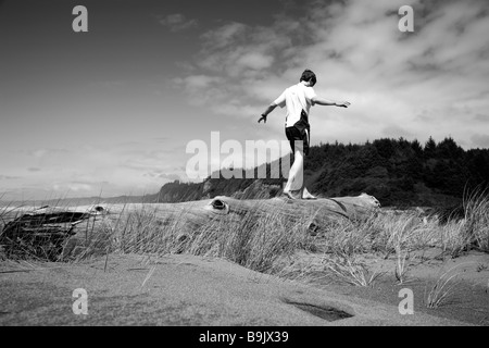A man balances on a log near the beach in Redwoods National Park, California. - Stockfoto