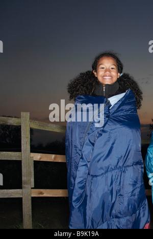 Girl in sleeping bag at dusk - Stock Photo