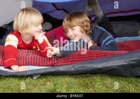 Two boys looking out of tent - Stock Photo