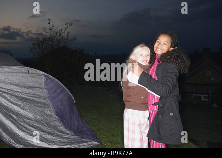 Girls in near tent at dusk - Stock Photo