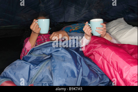 Girls with hot drink in tent - Stock Photo