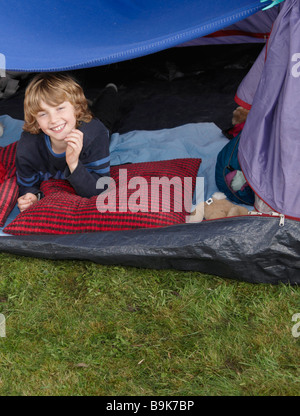 Boy looking out of tent - Stock Photo