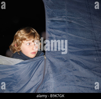 Boy looking out of tent at dusk - Stock Photo