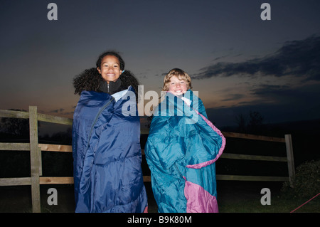 Girl and boy in sleeping bags at dusk - Stock Photo