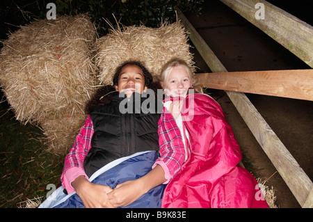 Girls in sleeping bags on haybales - Stock Photo